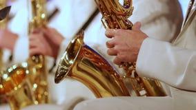 Una mano del ` s del hombre en un traje blanco en una banda de jazz en un saxofón del oro Primer almacen de video