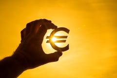 Una mano del ` s del hombre lleva a cabo el símbolo euro contra la luz del sol fotos de archivo libres de regalías