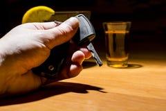 Una mano del ` s del hombre que lleva a cabo llaves del coche en una barra Fotos de archivo libres de regalías