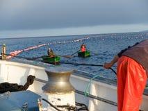Una mano del ` s del pescatore che fissa una corda e le barche Immagine Stock