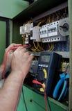 Una mano del trabajador del electricista que prueba la máquina industrial Imagen de archivo