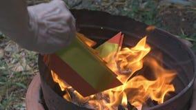 Una mano dell'uomo che cade la banconota di inferno o di Joss Papers per bruciare in serbatoio di acciaio per gli antenati in nuo stock footage