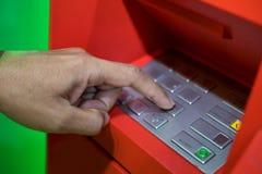 Una mano dell'uomo che imposta codice di PIN/pass sulla tastiera della macchina di ATM/bank fotografie stock