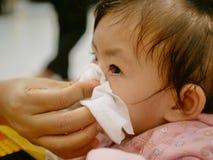 Una mano della madre che pulisce il suo naso corrente della figlia immagine stock libera da diritti