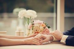 Una mano della tenuta della tenuta della coppia sposata mentre sedendosi dalla tavola in caffè, nei precedenti di un mazzo di bel fotografie stock libere da diritti