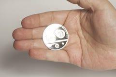Una mano della tenuta del bitcoin del centesimo Fotografia Stock