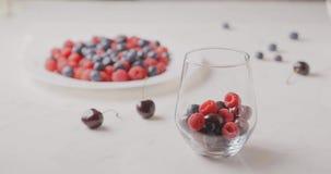 Una mano delle donne riempie un vetro di bacche rosse mature - lamponi, ciliege, mirtilli su una tavola bianca e vaghi stock footage