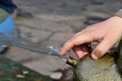 Una mano di 5 anni del ragazzo della corrente commovente dell'acqua dalla fontana Fotografia Stock
