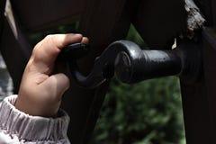 Una mano di 3 anni della ragazza della porta di apertura con la maniglia forgiata Immagini Stock