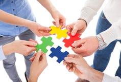 Una mano di cinque genti con il puzzle Immagine Stock Libera da Diritti