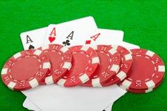 Una mano di mazza di quattro schede e chip di gioco degli assi Immagine Stock