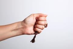Una mano e un rosario immagine stock