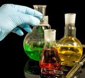 Una mano en una cristalería del guante y de laboratorio en un primer negro del fondo Foto de archivo libre de regalías