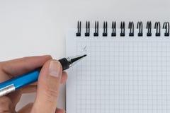 Una mano está escribiendo en el cuaderno de la página en blanco foto de archivo