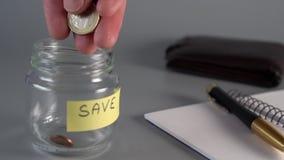 Una mano está lanzando centavos y euros de las monedas en un tarro de cristal de ahorros con la RESERVA de la inscripción almacen de video