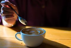 Una mano está sosteniendo una cuchara para intentar el café del latte foto de archivo libre de regalías