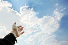 Una mano extendida al cielo imagenes de archivo