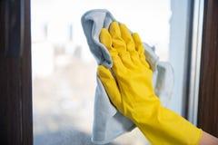 Una mano femenina en lavados de goma amarillos brillantes de los guantes limpieza de la ventana con un trapo suave fotografía de archivo