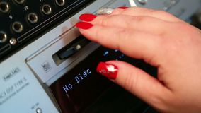 Una mano femenina inserta un mini disco en un jugador plateado almacen de metraje de vídeo