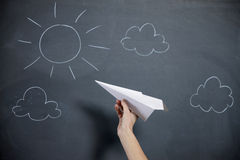 Una mano femenina se prepara para lanzar un aeroplano de papel imagen de archivo