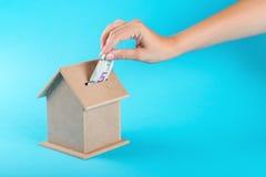 Una mano femminile che mette i cinque dollari in un salvadanaio Il concetto del risparmio finanziario per comprare una casa Fotografia Stock