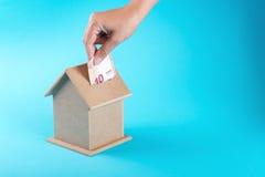 Una mano femminile che mette un euro dieci in un salvadanaio Il concetto del risparmio finanziario per comprare una casa Immagini Stock