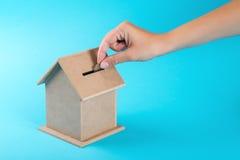 Una mano femminile che mette una moneta in un salvadanaio Il concetto del risparmio finanziario per comprare una casa Fotografia Stock