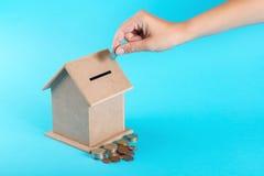 Una mano femminile che mette una moneta in un salvadanaio Il concetto del risparmio finanziario per comprare una casa Fotografia Stock Libera da Diritti