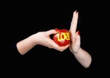 Una mano femminile che propone una mela con un amore di parola e il othe Immagini Stock