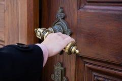 Una mano femminile che tiene una manovella da una vecchia porta di legno immagini stock libere da diritti