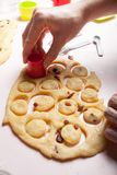 Una mano femminile produce i biscotti rotondi della pasticceria Preparando per il Natale, una famiglia cuoce la ricetta immagini stock
