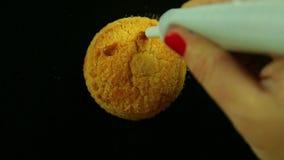 Una mano femminile tiene un tubo di latte condensato e disegna gli emoticon divertenti sui biscotti Rivestimenti di tempo stock footage