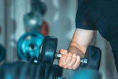 Una mano fuerte de un atleta con una pesa de gimnasia fotografía de archivo libre de regalías