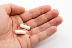 Una mano humana que sostiene dos píldoras blancas imagenes de archivo