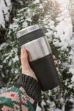 Una mano i che tiene una termo tazza riutilizzabile, termos, tazza di viaggio sui precedenti di una conifera innevata, inverno fu fotografie stock libere da diritti