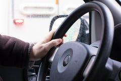 Una mano insegura que conduce el volante del ` s del coche Imagen de archivo libre de regalías