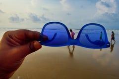 una mano llevando a cabo sunglass delante del mar Y el caminar de tres personas foto de archivo