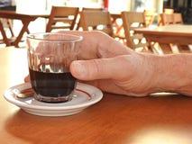 Una mano maschio che tiene una tazza di vetro con caffè, su una tavola all'aperto della barra immagini stock libere da diritti