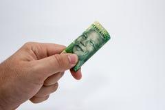 Una mano masculina caucásica que lleva a cabo una nota de 10 Rand South African Esta imagen tiene un fondo llano fotografía de archivo