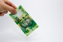 Una mano masculina caucásica que lleva a cabo una nota de 10 Rand South African Esta imagen tiene un fondo llano imágenes de archivo libres de regalías