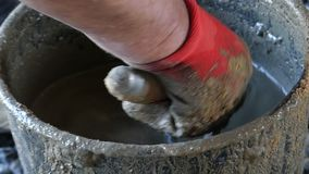 Una mano masculina en guante mezcla el cemento y el agua para conseguir el mortero metrajes