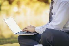 Una mano masculina está funcionando con su ordenador portátil en un parque imagenes de archivo