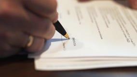 Una mano masculina que firma un impreso existencias Tiro del primer Acuerdo de contrato de firma del negocio del hombre de negoci almacen de video