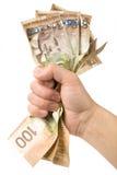 Una mano in pieno dei dollari canadesi Immagini Stock