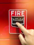 Una mano que alcanza y que tira de un interruptor rojo la alarma de incendio Alarma de incendio roja Fotografía de archivo libre de regalías