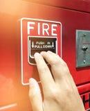 Una mano que alcanza y que tira de un interruptor rojo la alarma de incendio Alarma de incendio roja Fotos de archivo libres de regalías