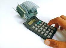 Una mano que calcula algo con la calculadora con la pila de dinero del efectivo aislada en el fondo blanco fotos de archivo libres de regalías