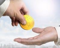 Una mano que da a signo de interrogación la moneda digital a otra Foto de archivo