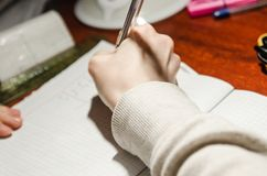 Una mano que escribe con una pluma fotos de archivo