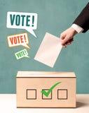 Una mano que pone un resbalón de votación en una votación Foto de archivo libre de regalías